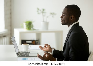 Calm peaceful african american businessman in suit meditating in office, black employee executive practicing yoga at workplace for mental emotional balance, no stress at work free relief, side view