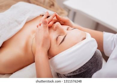 Calm and peaceful. Nice young woman closing her eyes while feeling relaxed during the facial cleansing procedure