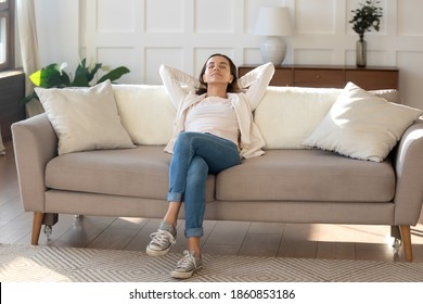Calm and positive. Happy serene young female relaxing on couch at living room leaning back on pillows. Woman taking break of household chores, breathing fresh air, dreaming about spending weekend