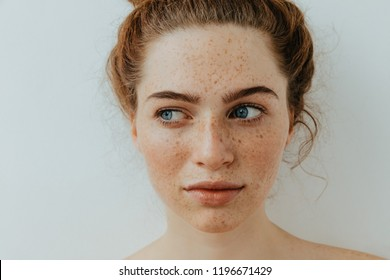 Calm and pretty. Close-up. Beautiful blue eyed girl with freckles is looking away, on a white background