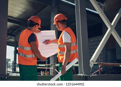 Calm professional builder in green and orange uniform standing outdoors next to his colleague and pointing to the drawing in his hands