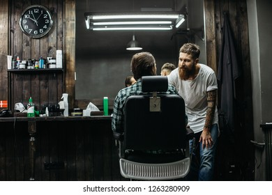 Calm professional long bearded barber standing next to the mirror and bending his back while leaning to the client