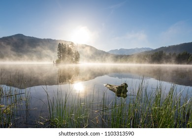 Calm reflecting lake with steam coming off the water and creating a foggy mysterious feel while surrounding an island during sunrise in the Kootenai's of British Columbia, Canada