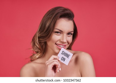 Calm and relaxed.  Attractive young woman looking at camera and smiling while standing against pink background