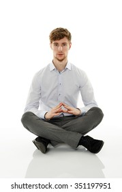 Calm and relaxed businessman meditating, sitting with his legs crossed