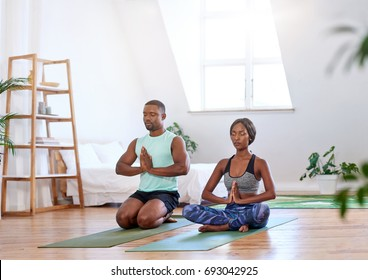 Calm relaxed couple meditating at home doing yoga relaxation