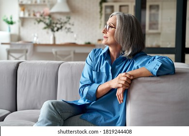 Calm relaxed mature older woman relaxing sitting on couch at home. Peaceful middle aged grey-haired lady resting on sofa in modern living room enjoying lounge and no stress, looking away, thinking. - Shutterstock ID 1819244408