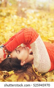 Calm relaxed woman profile portrait, take a rest lying in autumn  leaves in park, closed eyes, many bracelets on hands, outdoor