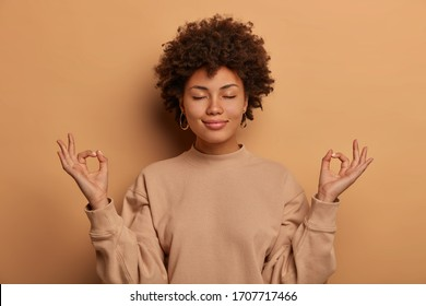Calm relieved dark skinned woman takes deep breath, keeps hands sideways in zen gessture, reaches nirvana and practices yoga, stands with closed eyes, stands stress free against brown background