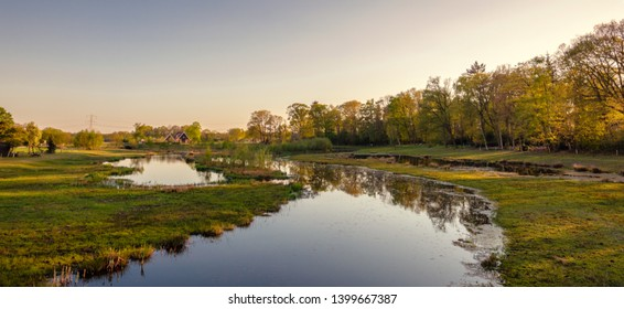 Calm river along a walking trail in a Dutch farm landscape during sunset. It is located near the small neighbourhood called Tusveld, near the town of Almelo in the Eastern Netherlands.