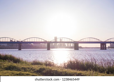 a calm river and an arch bridge and green grass and blue sky at Hangang Park, Seoul, South Korea