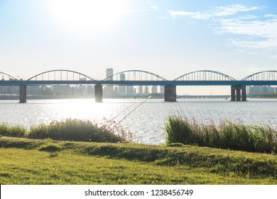a calm river and an arch bridge and two fishing rods and green grass and blue sky at Hangang Park, Seoul, South Korea