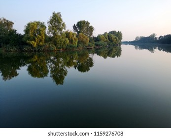 Calm river in beautiful sunrise, green natural lanscape. Peaceful morning.
