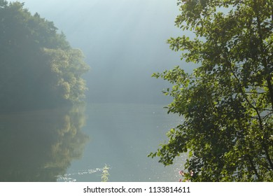 Calm river in the morning sun with dust