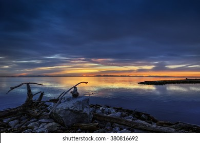 Calm river at sunrise, rocks and driftwood on the shore