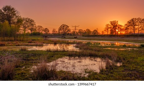 Calm river and two ponds along a walking trail in a Dutch farm landscape during sunset. It is located near the small neighbourhood called Tusveld, near the town of Almelo in the Eastern Netherlands.