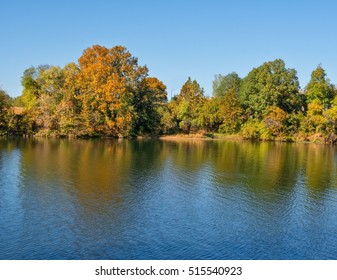 A calm riverbank with fall foliage reflections of tree lined bank