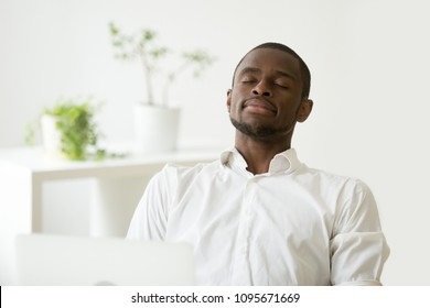 Calm satisfied African American businessman relaxing and meditating at workplace, having eyes closed, person practicing emotions control, preserving balance, managing stress. Peace, recovery concept