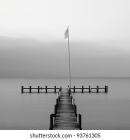 Calm scene in black and white with wooden jetty on a cold day