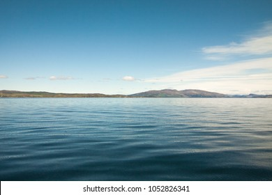 calm sea, cloud, sky and far islands on the horizon. The place is in Small Isles in north atlantic ocean travel by yacht from Isle of Skye, Scotland