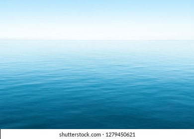 Calm sea or ocean. Blue or azure water color. Clear and blue sky. Sunny summer weather. Beach, cruise, tropical island.