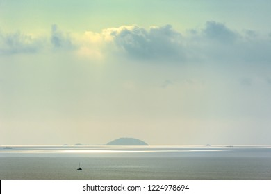 CALM SEA ON A HAZY DAY. Scenic view of calm sea on a hazy day with a yacht and islands in a distance.