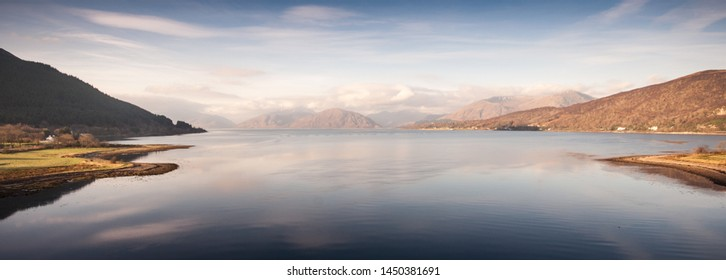 Calm sea waters on Loch Linnhe reflect blue skies and the snow-capped mountains of the Ardnamurchan Peninsula on the west coast of the Highlands of Scotland.