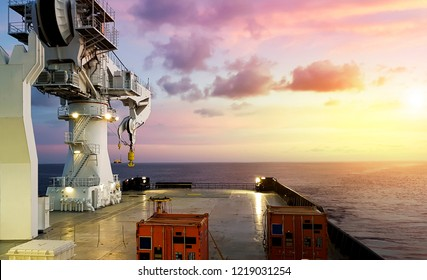calm seas as seen from a modern offshore vessel with containers loaded on deck and large crane swung out to its aft