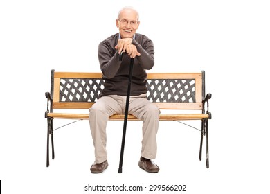Calm senior gentleman with a cane sitting on a wooden bench and looking at the camera isolated on white background
