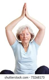 Calm senior woman doing relaxing yoga exercises