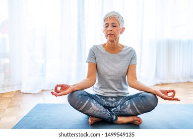 Calm senior woman relax, meditating in lotus position, peaceful aged female practice yoga at home relieve stress or renew energy, elderly lady do physical exercises following healthy lifestyle
