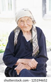 Calm senior woman sitting outdoors hands folded