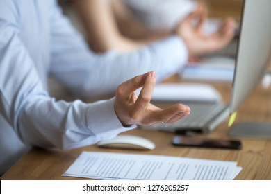 Calm serene man sitting at office desk holding hands in mudra doing yoga exercises taking break for stress relief concept for concentration and balance at workplace, meditation at work, close up view
