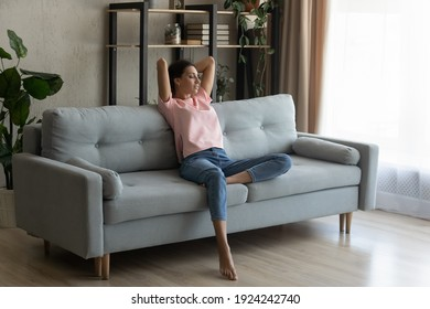 Calm serene pretty arabian woman rest relax on couch at home breath fresh air meditate enjoy free time on weekend. Peaceful young indian lady dreaming on sofa at modern living room nap relieve stress