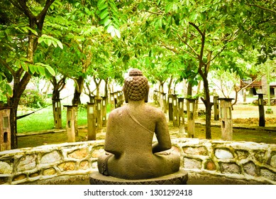 Calm sitting buddha stone rock statue meditating peacefully in the garden spa retreat under the tree and sunrise for peaceful zen yoga retreat for wedding couple honeymoon