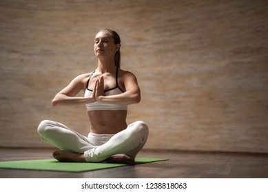 Calm slim lady sitting on the yoga mat and closing her eyes while meditating with hands in front of her chest