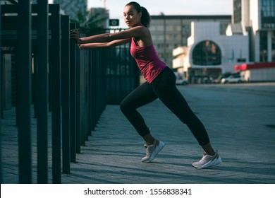 Calm slim sportswoman putting hands on the banister and using it in her training