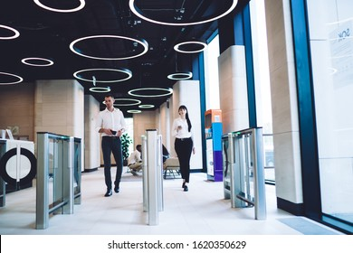 Calm smart colleagues in trendy formal wear going through automatic turnstile gates in hall of light modern building in downtown