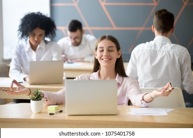 Calm smiling woman practicing office meditation in coworking space taking break for relaxation, mindful happy millennial student or employee feeling zen enjoying no stress free relief at work concept
