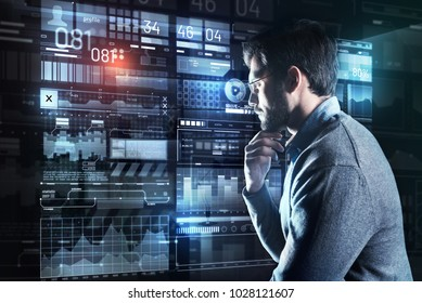 Calm specialist. Clever calm attentive programmer touching his beard and thoughtfully leaning to a transparent screen while analyzing the information on it