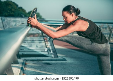 Calm sportswoman standing with foot on the banister and leaning towards it with closed eyes