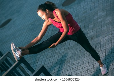Calm sportswoman in the street putting foot up on the banister and stretching muscles