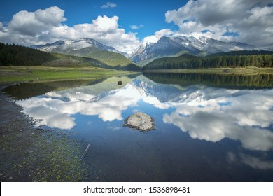 The calm still water of Mission reservoir and high peak snow covered mountains near St. Ignatius, Montana
