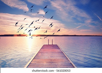calm summer evening, wooden Pier with stairway to water, sunset at the beach