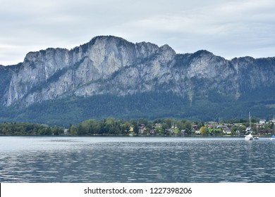 Calm surface of Attersee lake reflecting light with mountains in background on cloudy day.