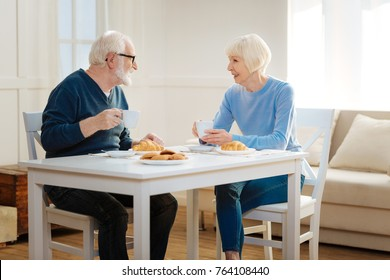 Calm talk. Attractive blonde female crossing legs while sitting at the table and turning head to her husband