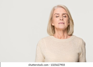 Calm tranquil mid aged old woman meditating breathing fresh air, serene mindful mature senior lady taking deep breath feeling no stress free relief harmony isolated on white grey studio background