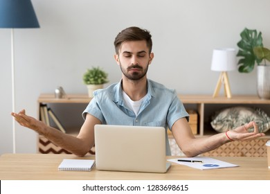 Calm tranquil young man taking break at work practicing yoga doing exercise at home office desk for stress relief relaxation focusing on concentration, mindful serene guy meditating at workplace