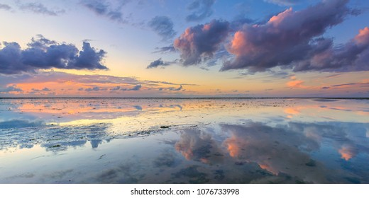 A calm and tranquil zen-like sunset at the beach with beautiful colours in pink and red with reflections on the water