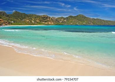 Calm tropical beach with mountains on Union Island